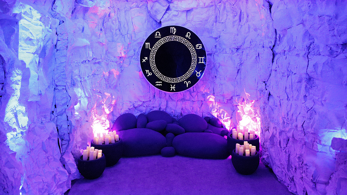 Candles flank a dark purple couch in a room with light purple crystal walls and a prominent circular wall art of zodiac symbols