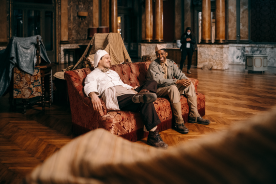 two men on a couch talking
