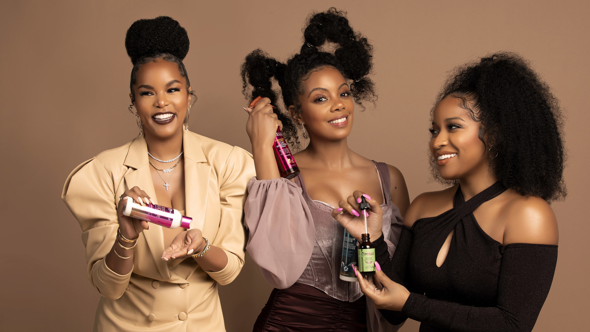 three black women smiling holding hair care products