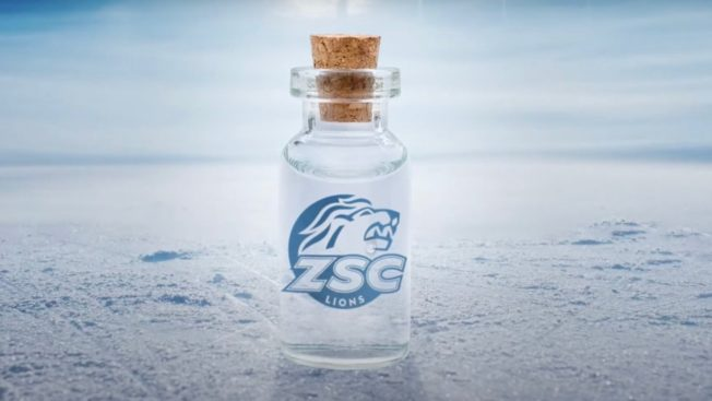 A clear bottle of water with a a cork stopper and a lion head logo sits on a sheet of ice