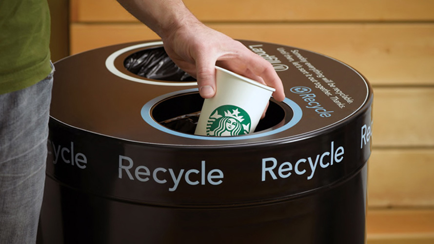 someone recycling a starbucks coffee cup