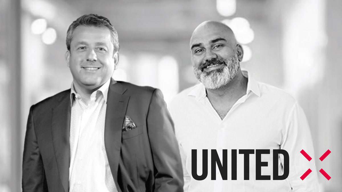 two men standing next to each other with united x logo in bottom right