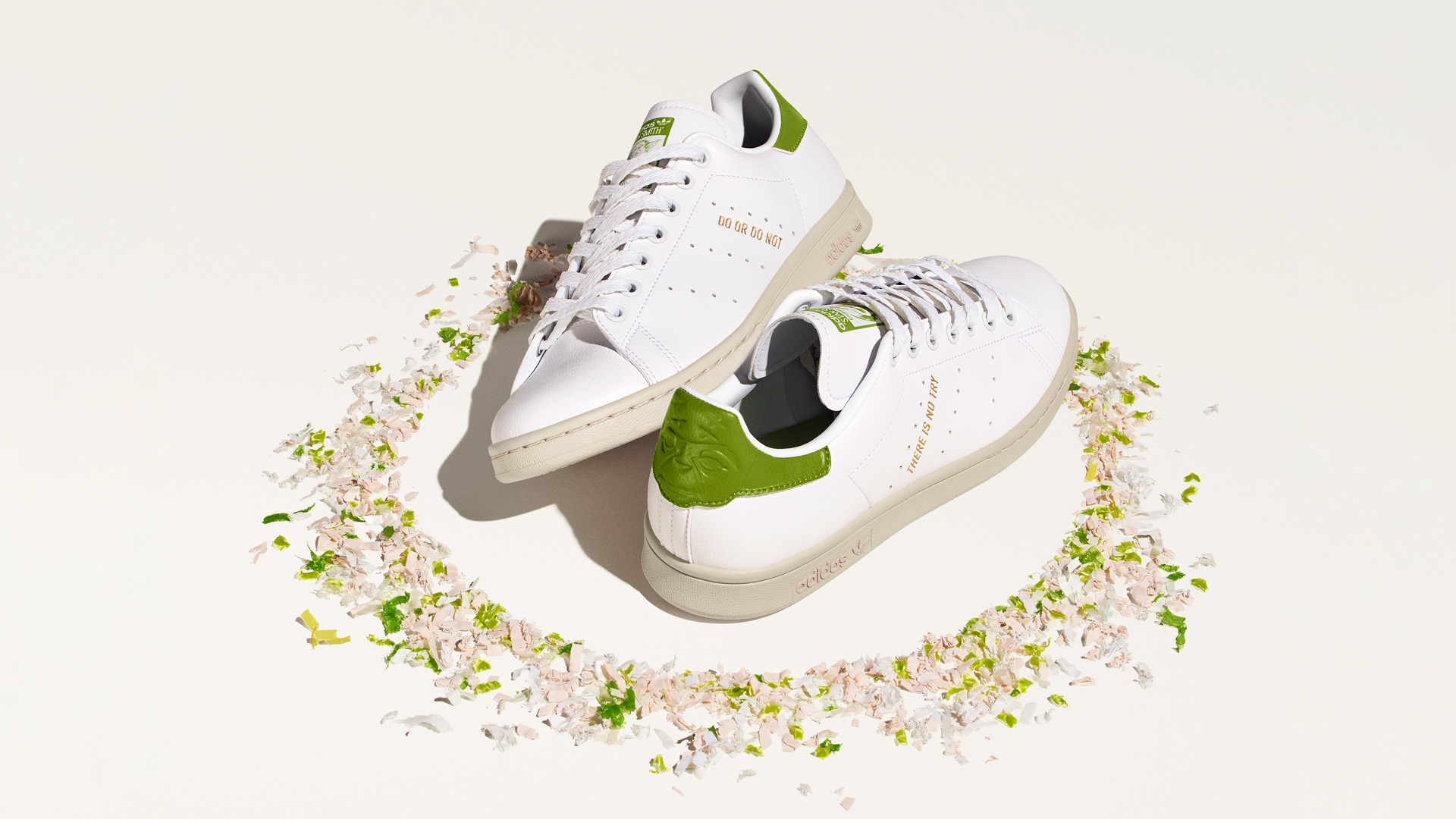 A pair of green and white sneakers surrounded by flower petals
