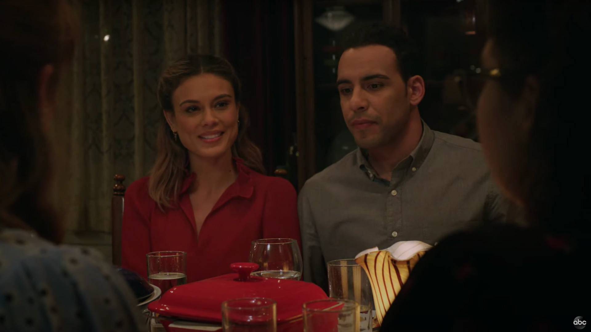 Actors Nathalie Kelley and Victor Rasuk sit side-by-side in a scene from the TV series The Baker and the Beauty.