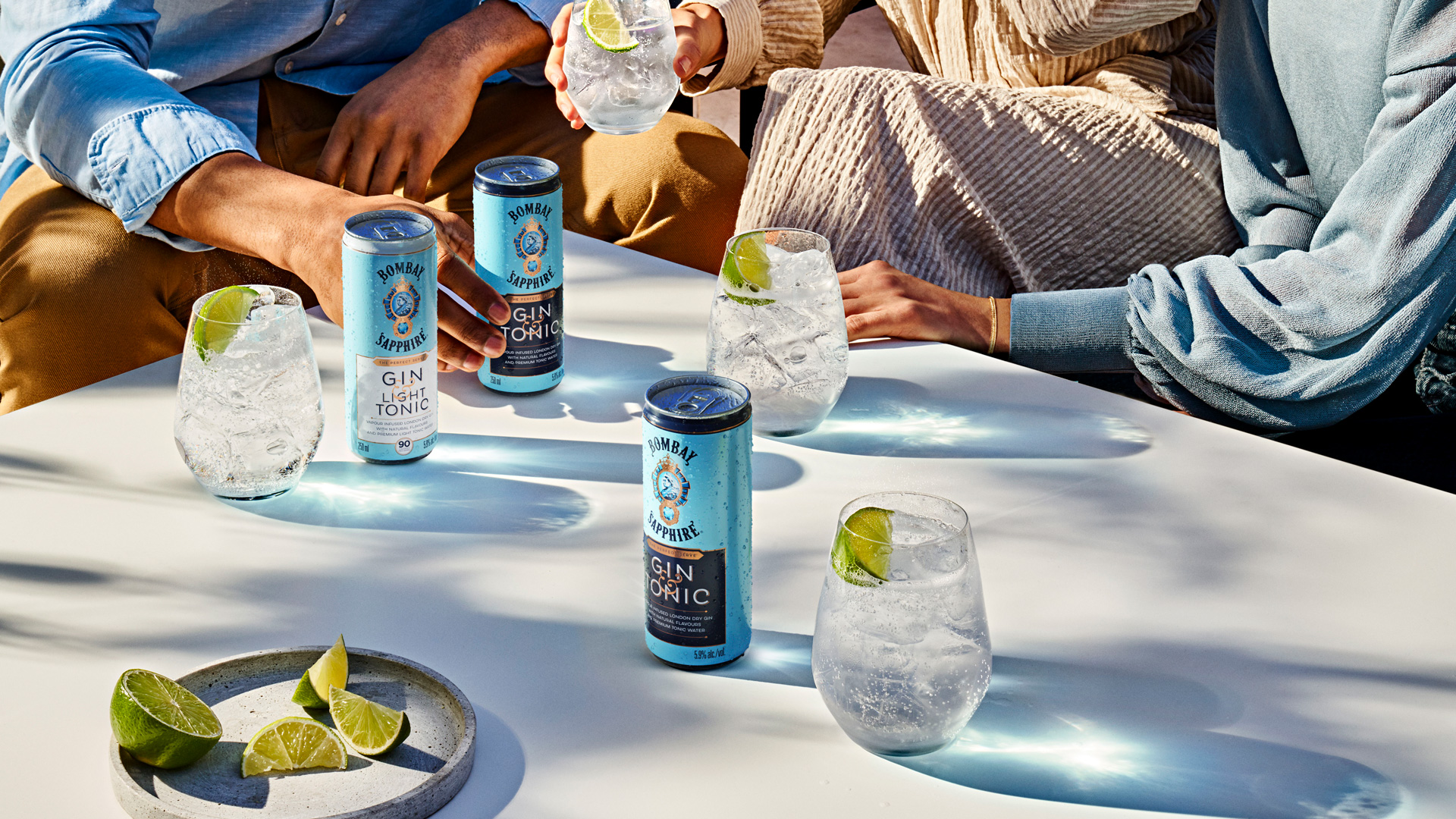 bombay sapphire gin and tonic cans on a table amid plates with hands in the background
