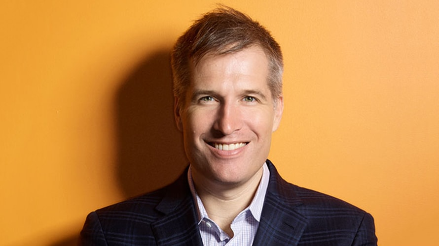 photo of Brian O'Kelley with an orange background