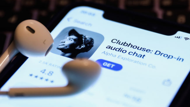 a phone screen showing the clubhouse app with a pair of airpods on top