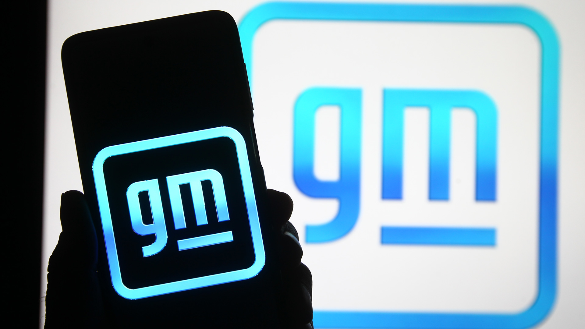 gm logo in background and gm logo on a shadowed phone screen
