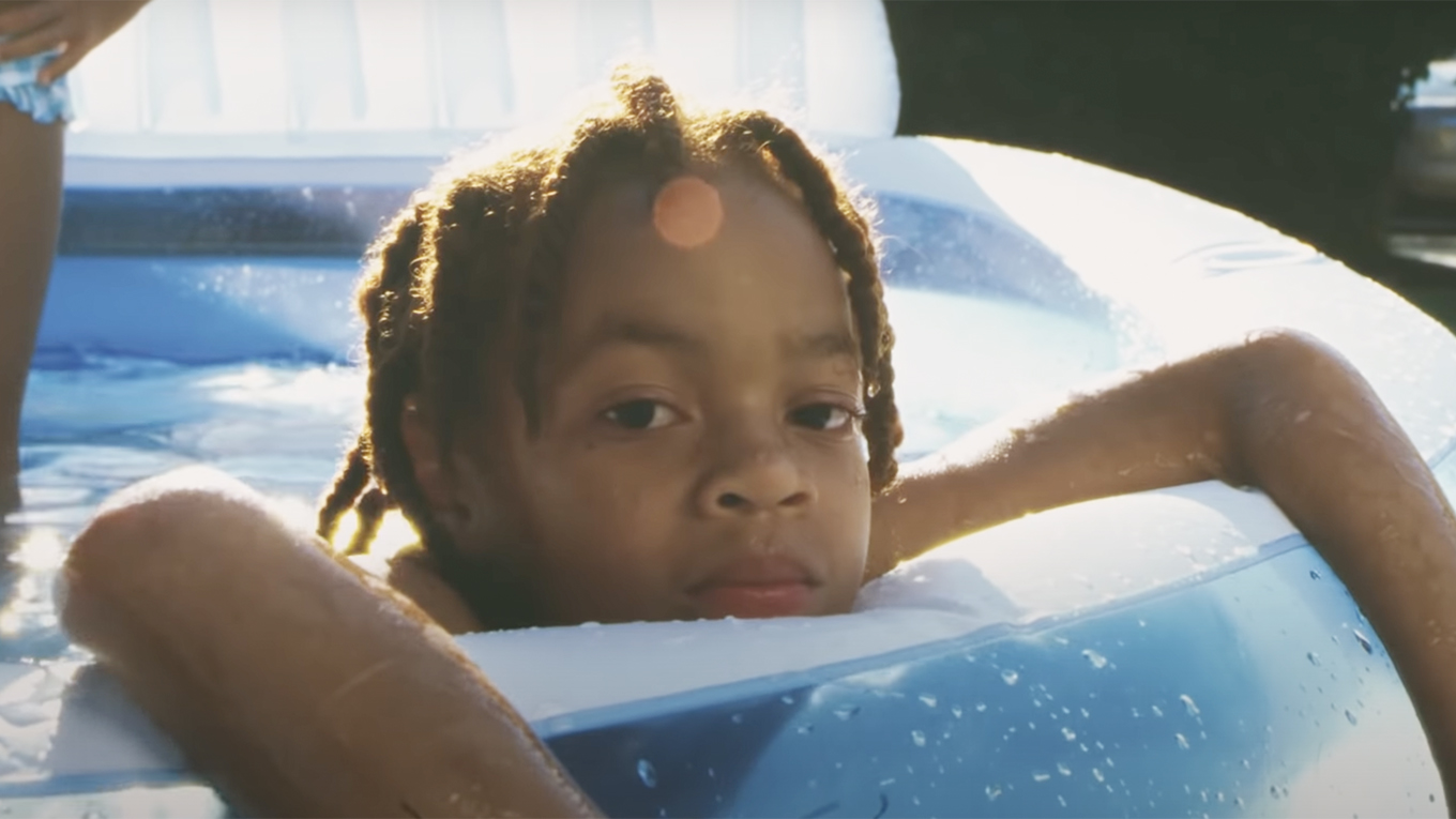 A young Black boy sits in an inflatable pool with his arms draped over the side as he looks toward the camera