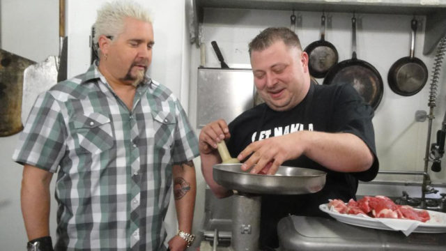 guy fieri standing next to a chef in a kitchen
