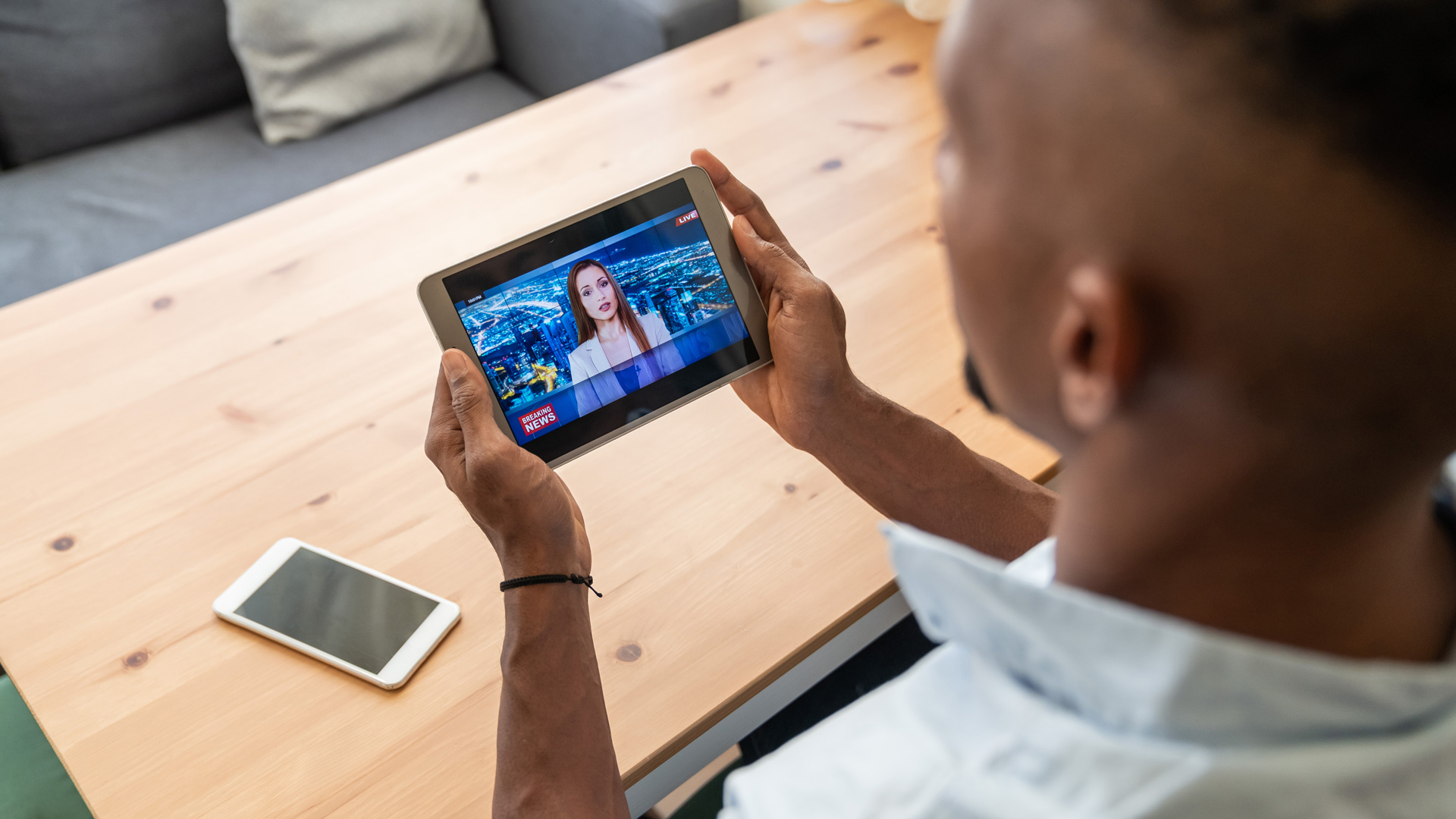 A photo of a man standing and watching the news on a tablet