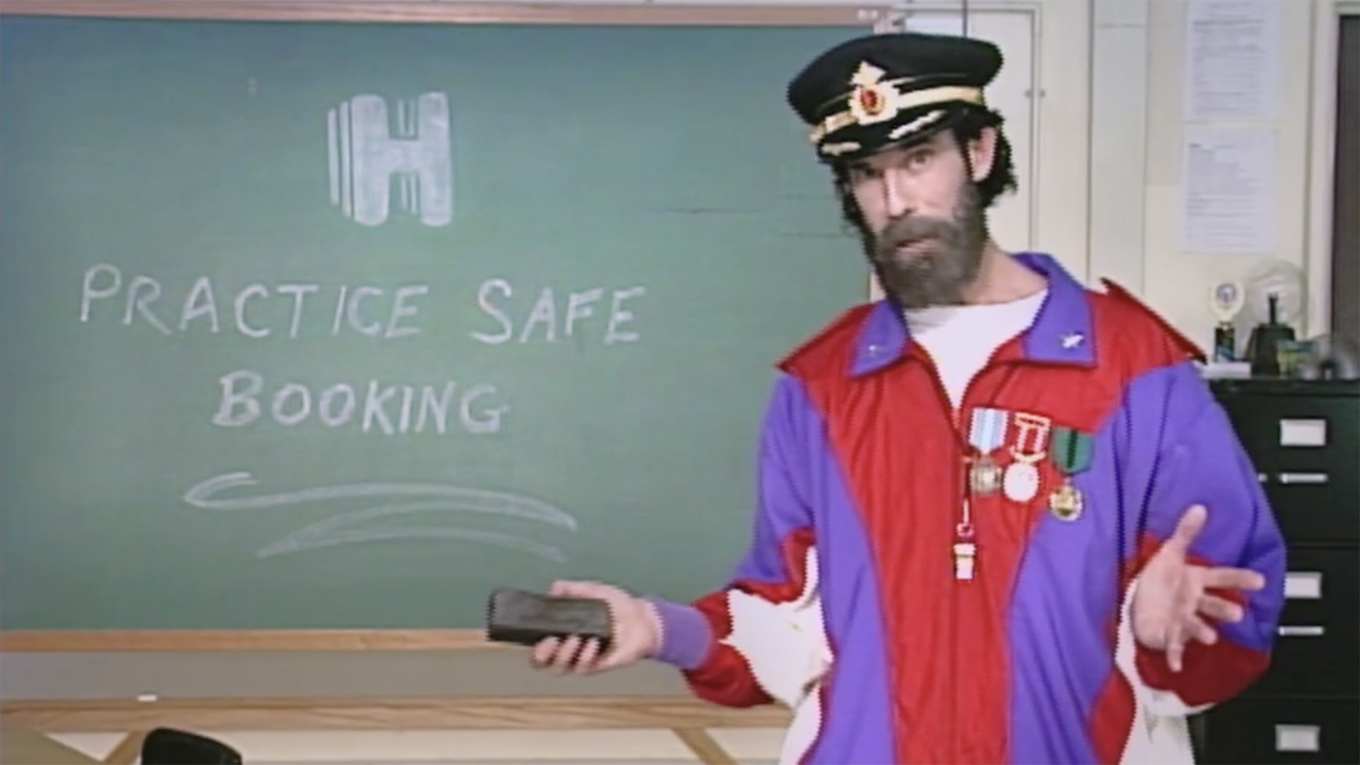 Hotels.com spokesman Captain Obvious wears a 1990s-themed red and purple outfit in front of a green chalkboard that says Practice Safe Booking