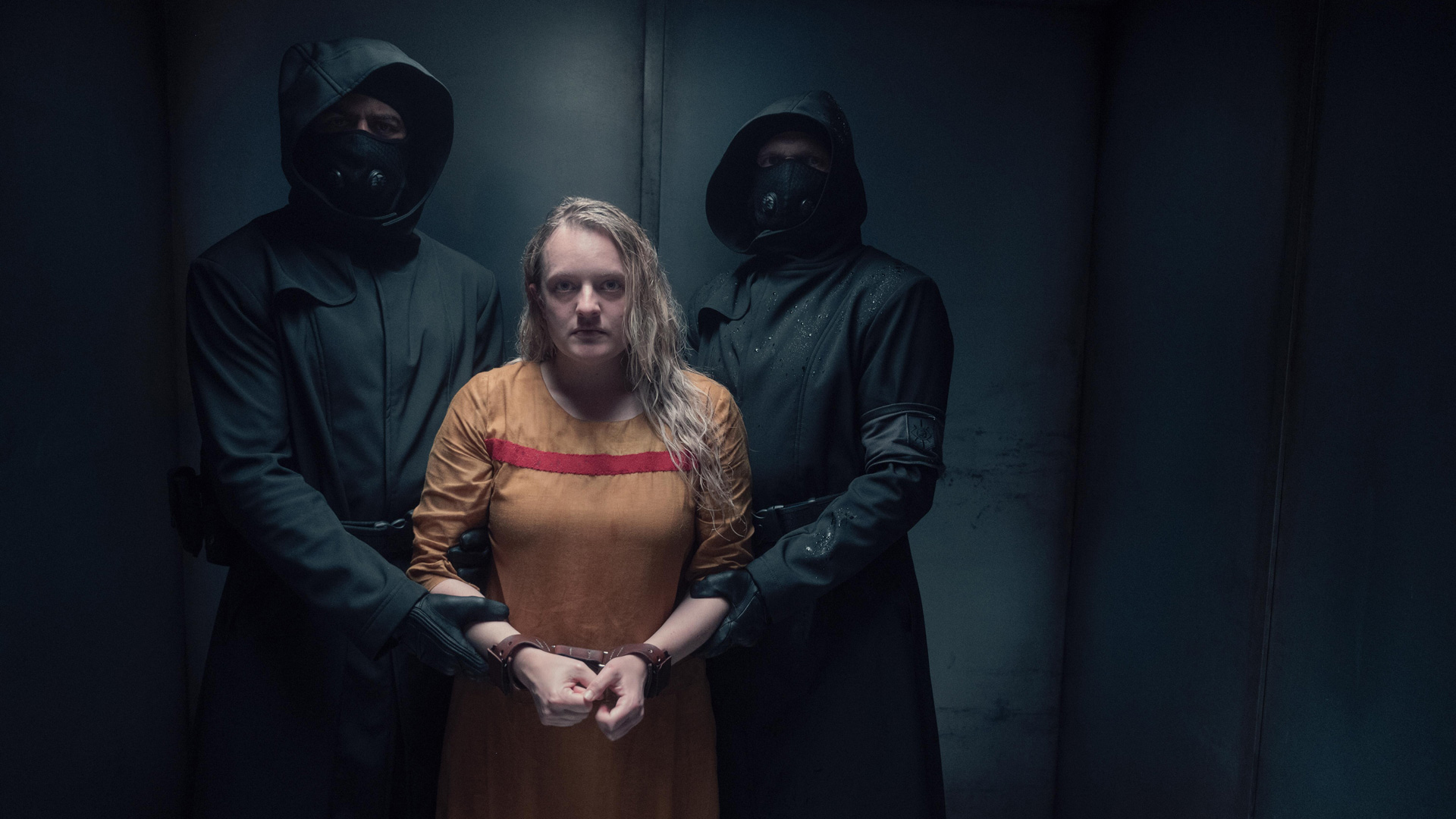 Elisabeth Moss, who plays Offred in The Handmaid's Tale, appears restrained by two hooded figures in a scene from the fourth season of the series.