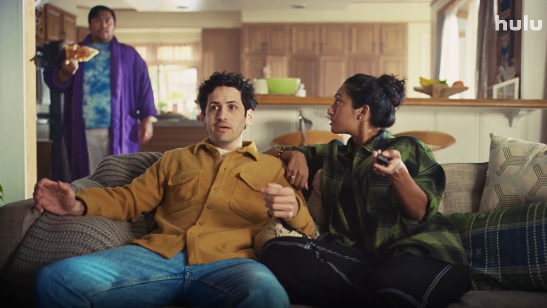two people on a couch eating and sitting talking to someone behind them eating a pizza