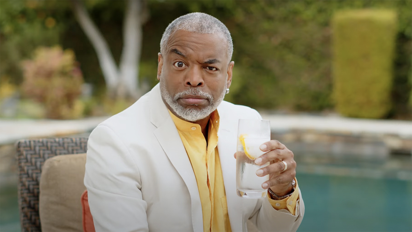 LeVar Burton wears a white sport coat and raises an eyebrow while trying a gin and tonic