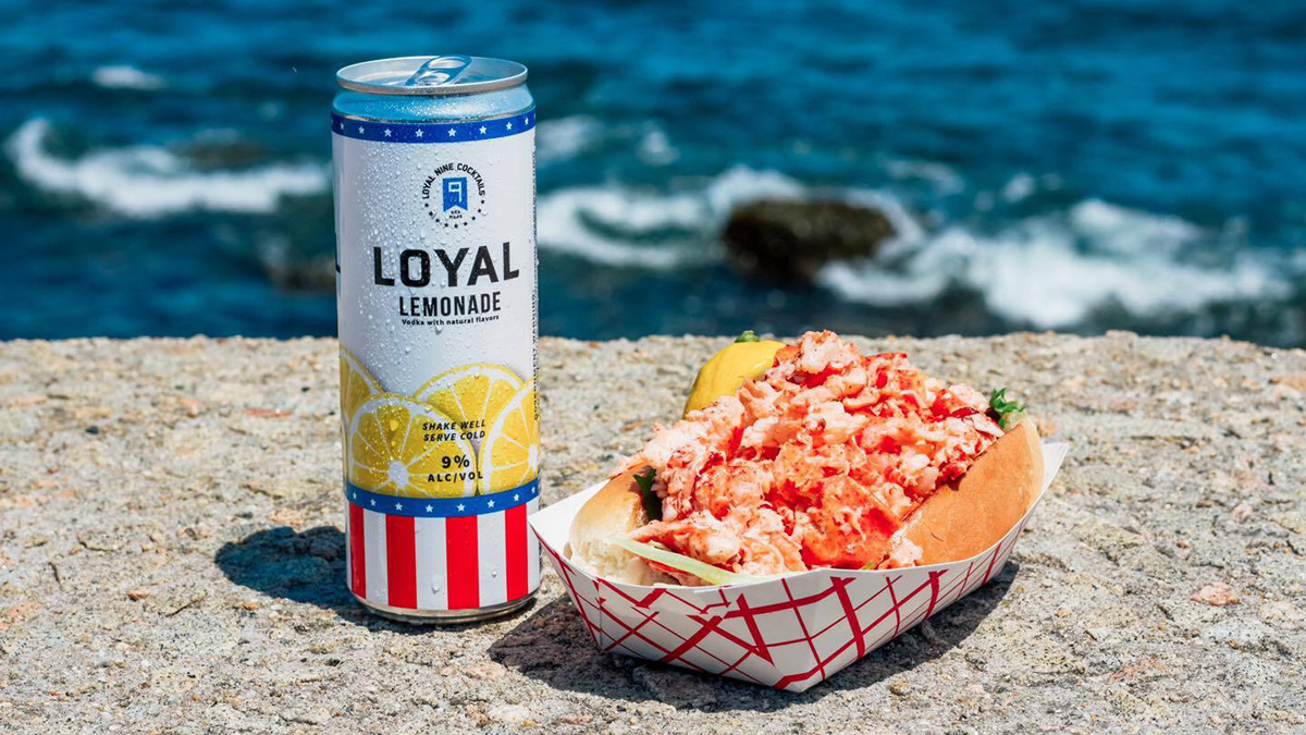 a loyal 9 drink next to a basket of a lobster roll in front of wave crashing