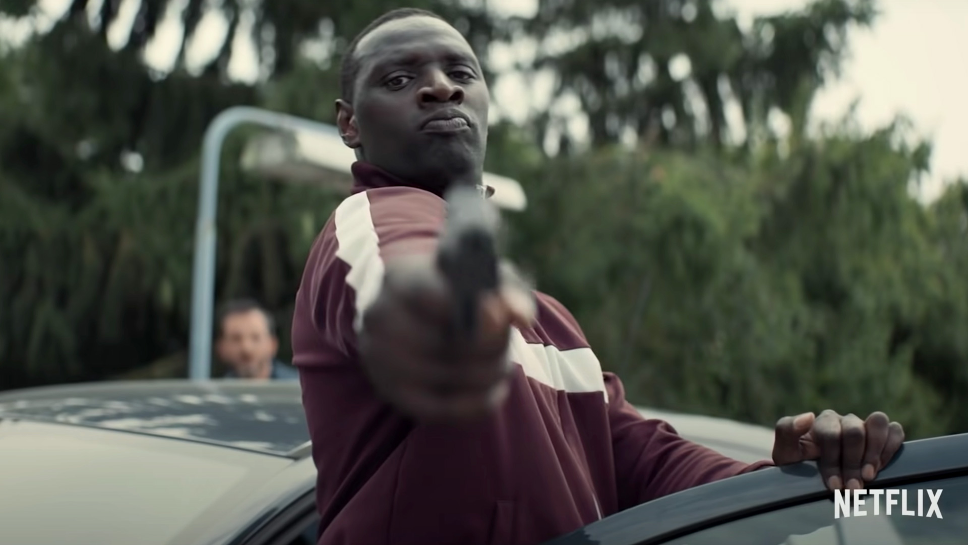 Omar Sy points a gun toward the camera in a scene from the French heist thriller Lupin.