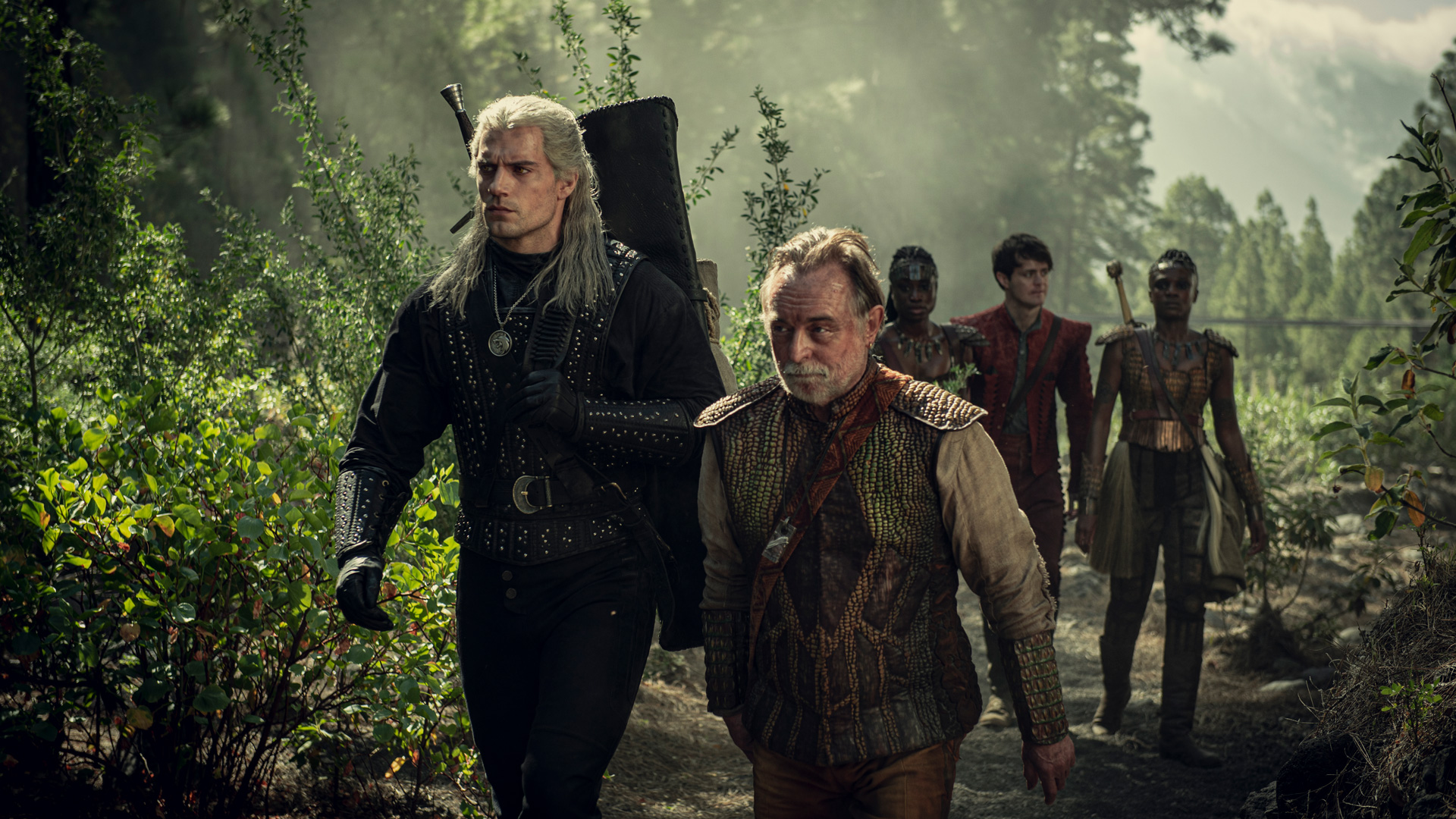 Henry Cavill appears in anforested outdoor setting in a still from the fantasy action series The Witcher.