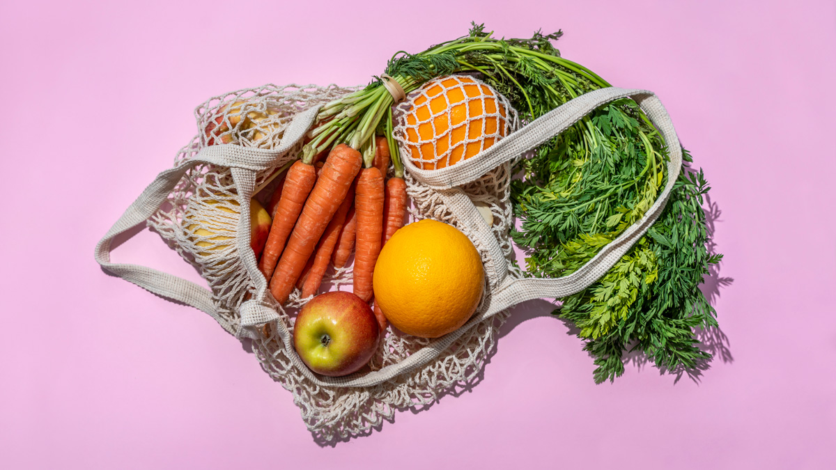 a net bad with carrots, oranges and apples in it on a plain pink background