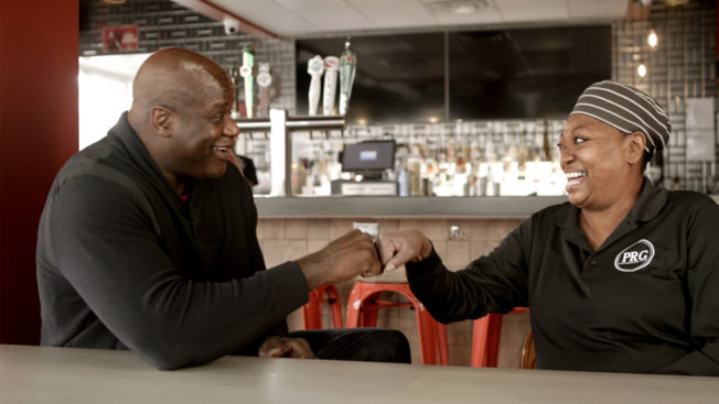 Shaquille O'Neal bumping fists with woman at a restaurant