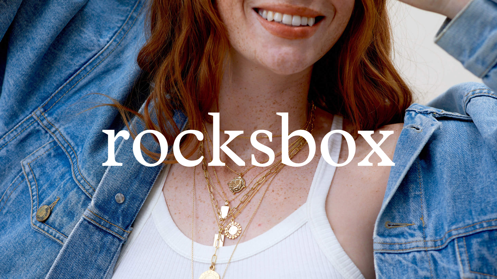 a freckly red head from the mouth down, showing a bunch of gold necklaces around her neck