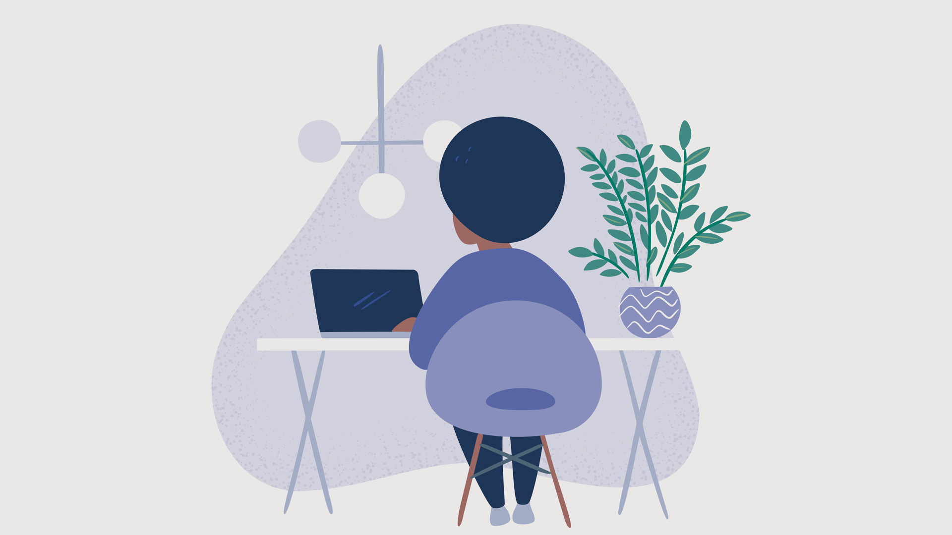 Person working at a desk with a plant next to them