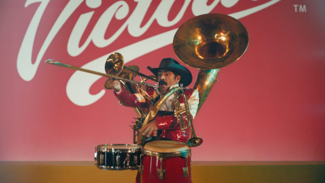 A one-man band in front of the Victoria logo