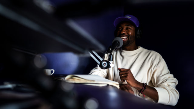 Man smiling in front of a podcast mic
