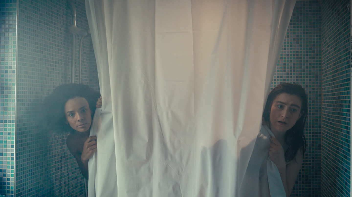 Two women look out from behind opposite ends of a shower curtain