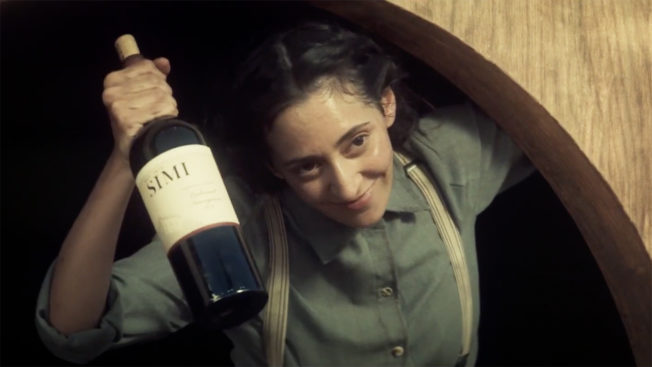 A woman in early 1900s clothing holds a Simi wine bottle while looking out from a rounded door