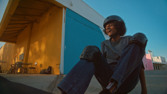 Laughing boy sitting on the ground after falling off of a skateboard