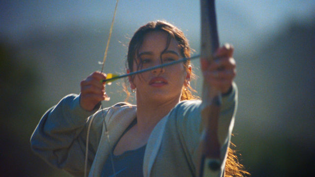 Singer Rosalía holds a bow and arrow.
