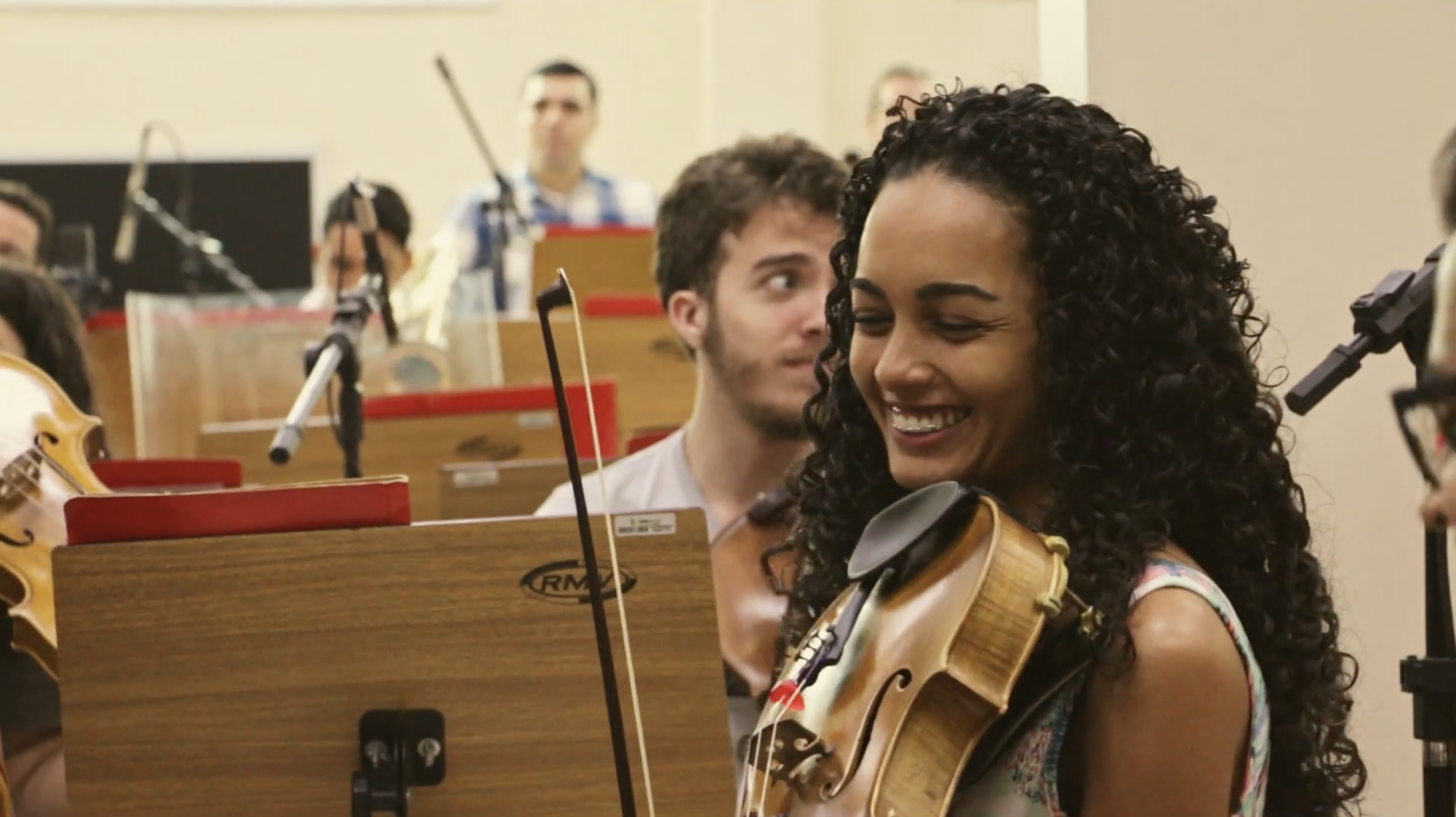 A young woman happily plays in an orchestra