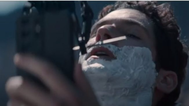 Actor Tom Ellis is shaved by a robot