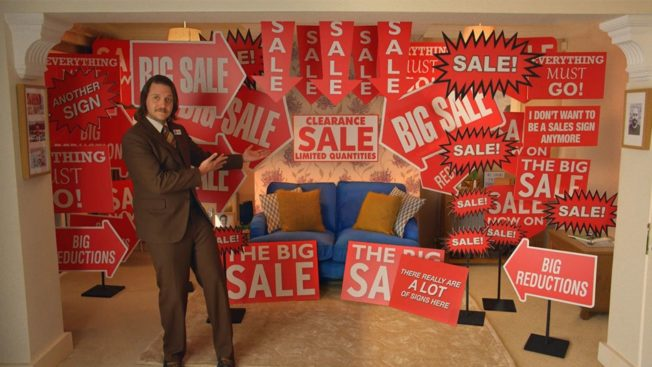 Sales signs surround a second hand couch