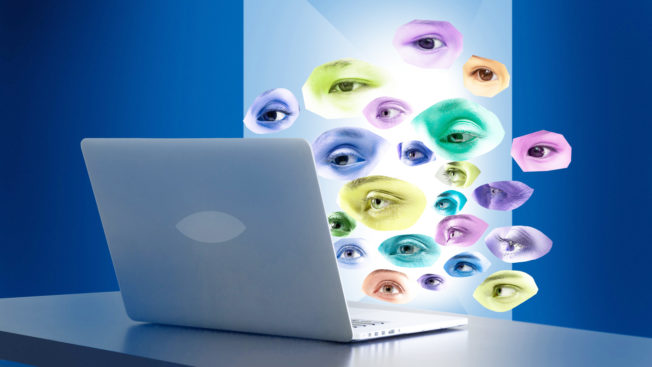 Disembodied eyes float over a laptop