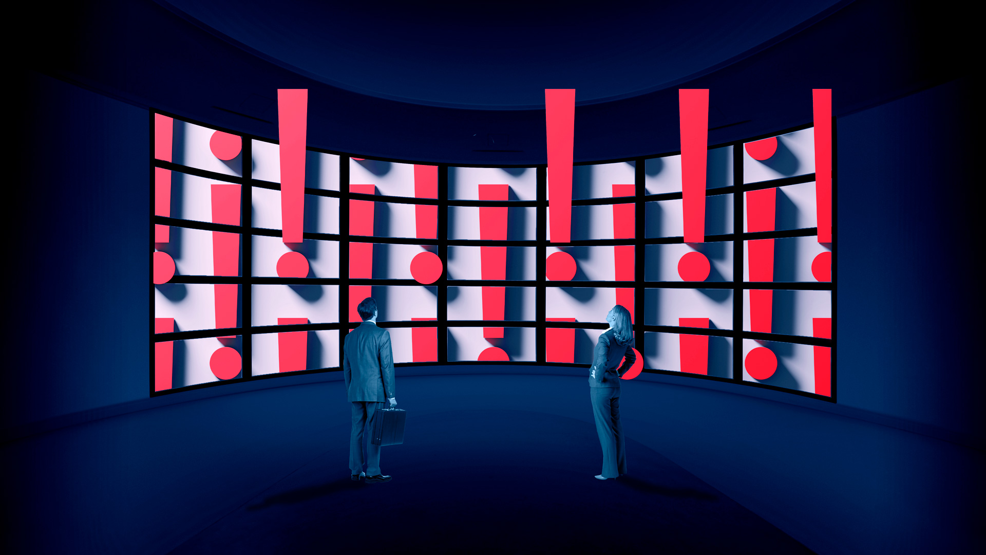 man and woman looking at a giant screen full of exclamation marks