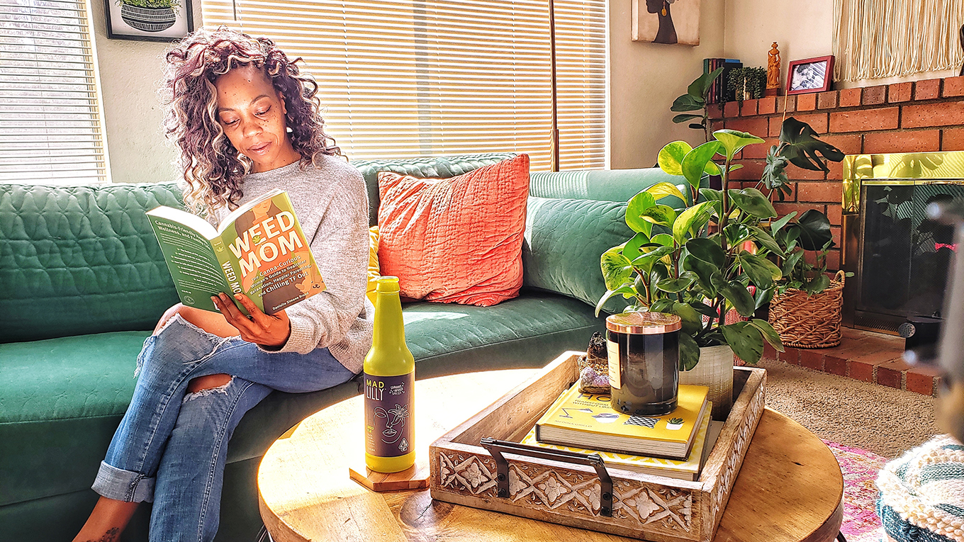 A woman sits on a couch reading a book titled Weed Mom with a bottle of Mad Lilly nearby