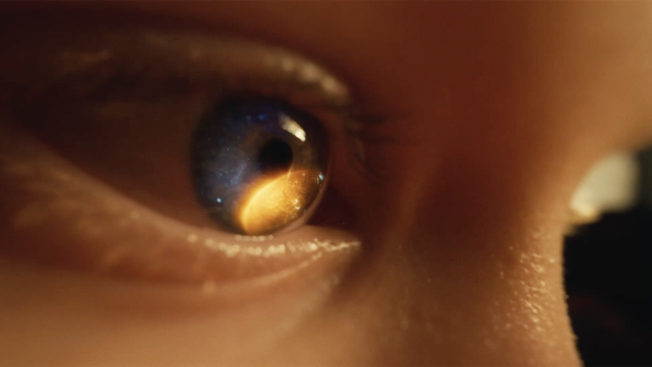 The reflection of a planet is seen in a close-up image of a child's eye