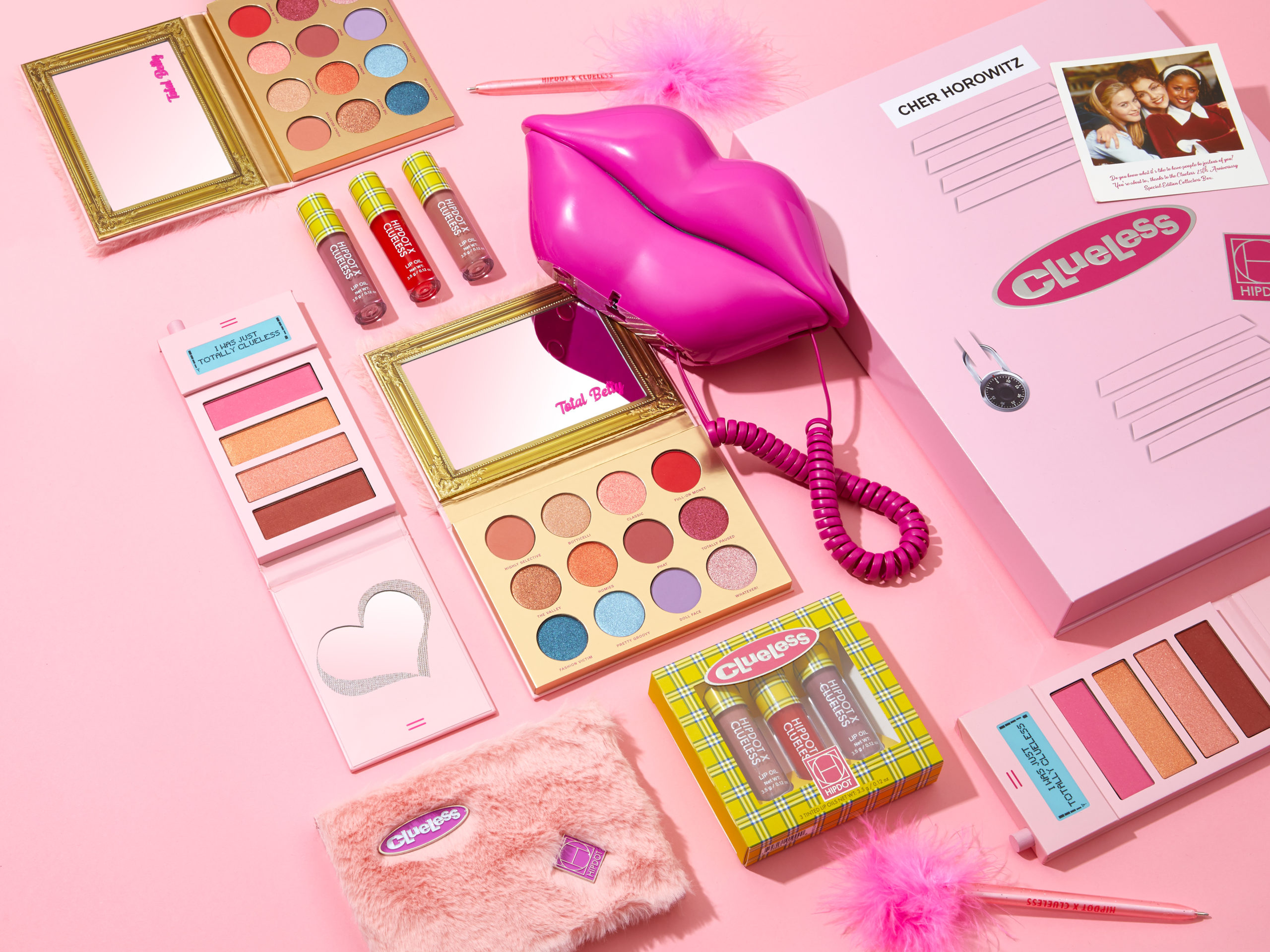 An array of makeup against a pink backdrop