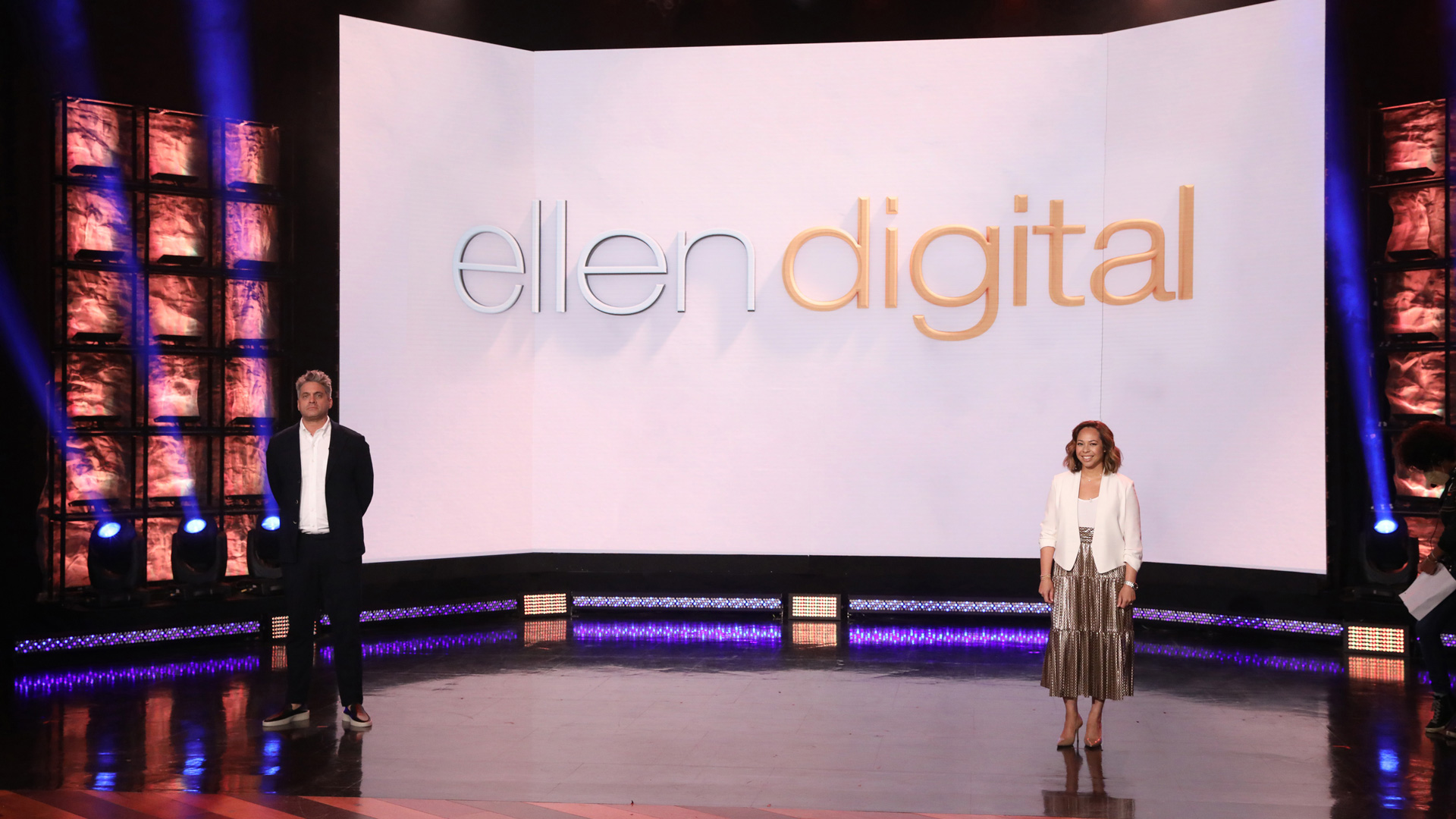 two people standing on a stage in front of a projection screen that says ellen digital