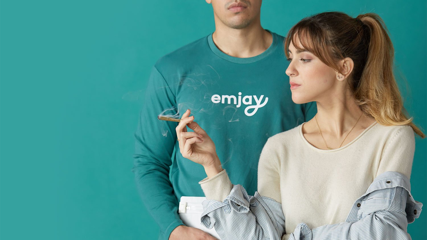 In a promotional image for cannabis delivery service Emjay, a woman holds a lit joint while standing next to a man in an Emjay long-sleeve shirt