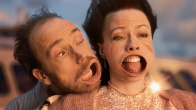 A man holds a woman from behind as their open mouths are distorted by high winds