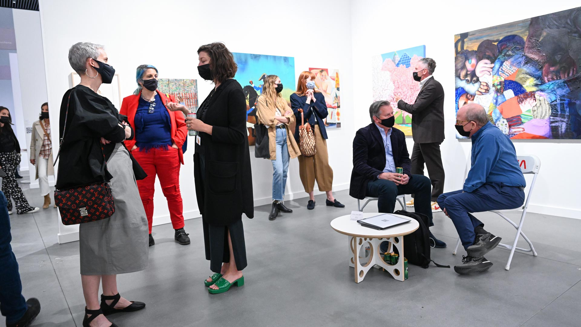 Group of people gathered in an art gallery admiring art and conversing.