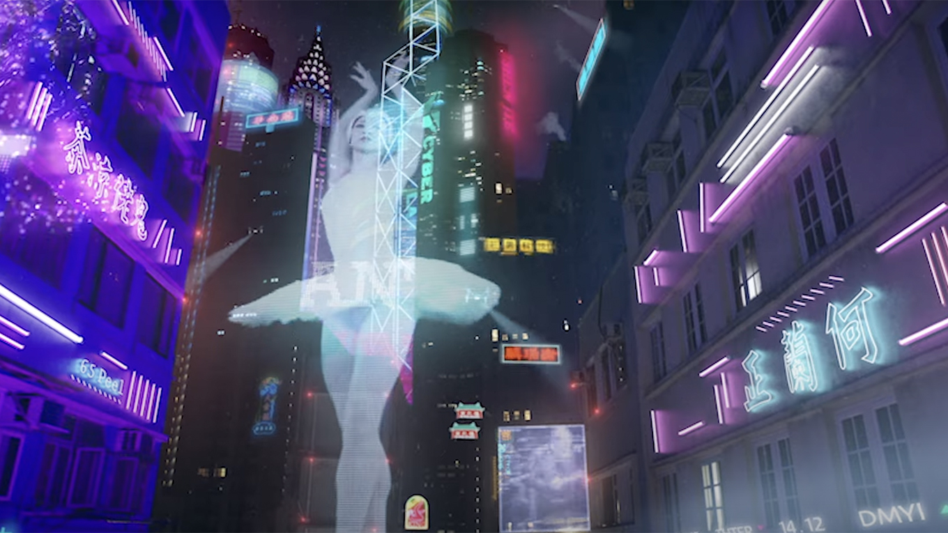 The image of a ballerina is projected across the side of a highrise in a futuristic cityscape