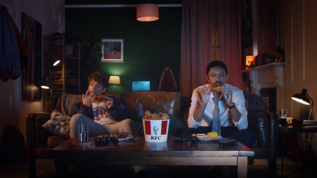 Two men enjoy a KFC on the couch