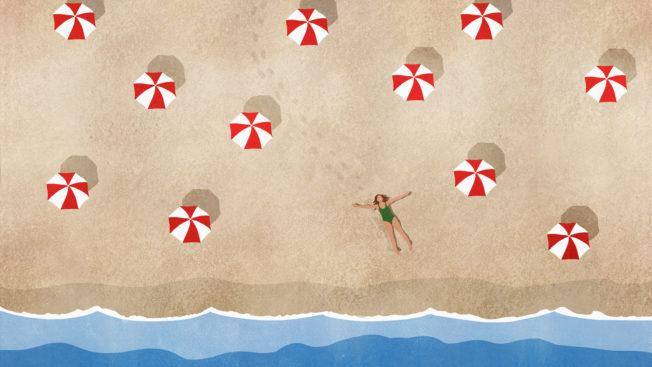 a person lying on a beach among red and white beach umbrellas