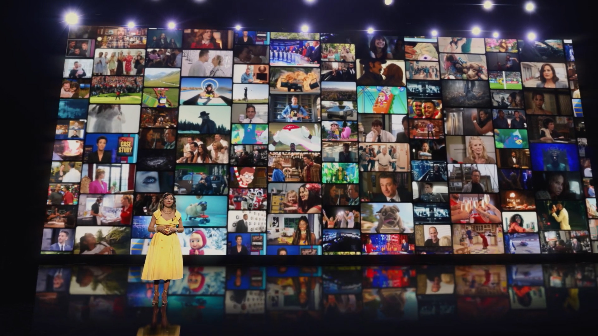 Linda Yaccarino, NBCUniversal's chairman of global advertising and partnerships, appears in front of a screen that has a mosaic of NBCUniversal programming images.