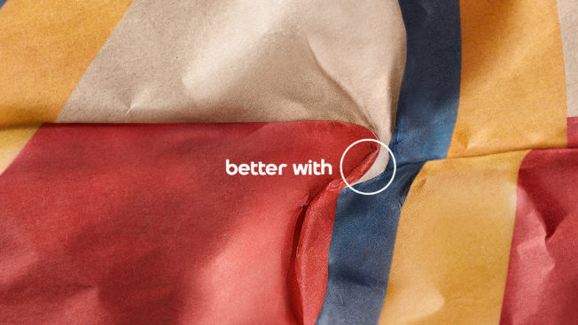 A McDonald's burger wrapper is crumpled up, revealing the shape of the Pepsi logo next to the phrase Better With