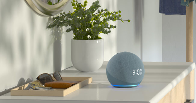 A smart speaker sits on an entryway table with sunglasses and a plant.